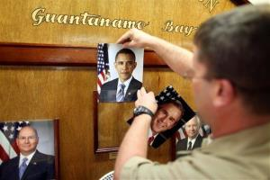 In this Jan. 20, 2009 photo, USNavy Chief Petty Officer Bill Mesta replaces an official picture of outgoing President George W. Bush with that of newly-sworn-in President Barack Obama.