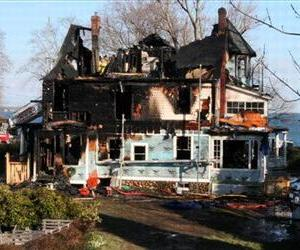 In this Dec. 25, 2011, file photo, firefighters investigate a house in Stamford, Conn., where an early morning fire left five people dead.