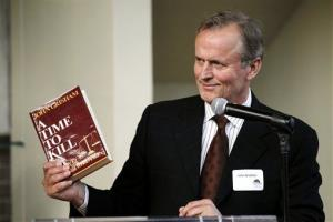 Writer John Grisham holds a copy of his book during the opening of the world premier of the stage adaption of 'A Time To Kill' at Arena Stage theater in Washington, Sunday, May 22, 2011.