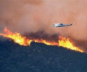 A water-dropping helicopter gets ready to make a drop in Point Mugu State Park during a wildfire that burned several thousand acres, Thursday, May 2, 2013, in Ventura County, Calif.