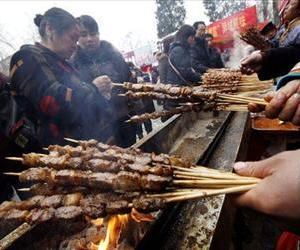 A vendor prepares lamb kebabs at a temple fair in Beijing Friday, Jan. 30, 2009.
