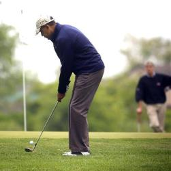 President Barack Obama, left, with Sen. Mark Udall, D-Colo., right, chips on the first hole of the golf course at Andrews Air Force Base, Md., Monday, May 6, 2013.