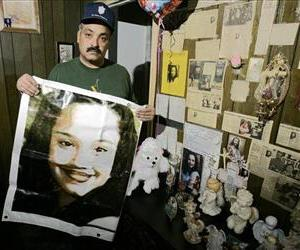 In this Friday, March 3, 2004 file photos shows Felix DeJesus, holding a banner showing his daughter's photograph, standing by a memorial in his living room in Cleveland.