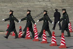 Chinese military soldiers march past traffic cones outside the Great Hall of the People in Beijing, China, Monday, March 4, 2013.
