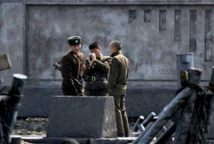 In this Wednesday, April 10, 2013 photo, North Korean soldiers chat as they stand guard on the river bank of the North Korean town of Sinuiju, opposite the Chinese border city of Dandong.