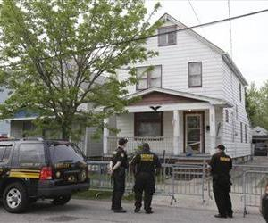 Sheriff deputies stand outside a house in Cleveland Tuesday, May 7, 2013, the day after three women who vanished a decade ago were found there.
