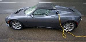 This 2011 file photo shows a Tesla Roadster Sport at a charging station in Portland, Ore.