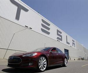 A Tesla Model S drives outside the Tesla factory in Fremont, Calif.