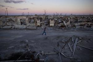 Former resident and tourist guide Norma Berg walks by a street in Epecuen, a village that once was submerged in water in Argentina.