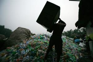 In this 2009 photo, a man prepares to dump plastic bottles at a recycling center in Beijing.