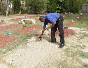 Bukhari Abdel-Alim of the Islamic Funeral Services of Virginia removes flowers from one of two newly dug graves at a cemetery in Doswell, Va. Tamerlan Tsarnaev is believed to be in one of them.