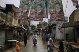Pakistani girls cross a street decorated with election posters showing cricket star-turned-politician Imran Khan, in Rawalpindi, Pakistan, Sunday, May 12, 2013.