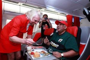AirAsia chief Tony Fernandes is served by that wacky, cross-dressing Richard Branson, who is paying up on a bet, Sunday, May 12, 2013.