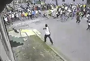 A shooting suspect in a white shirt, bottom center, shoots into a crowd of people Sunday in New Orleans.