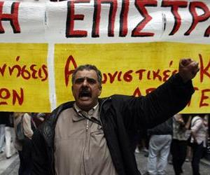 A state school teacher  shouts slogans, in front of a banner that reads No to The Civil Mobilization during a peaceful protest in central Athens on Monday, May 13, 2013