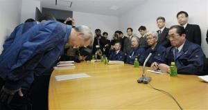 In this file photo, TEPCO exec Naomi Hirose, front left, bows in front of National Federation of fisheries cooperative official Ikuhiro Hattori, front right, and his delegation.