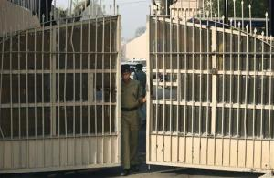 In this March 11, 2013 file photo, an Indian police officer prepares to close one of the gates at Tihar Jail, the largest complex of prisons in South Asia, in New Delhi, India.