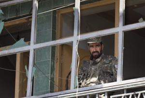 An Afghan Army soldier peers through a destroyed shop window at the scene where a suicide car bomber attacked a NATO convoy in Kabul, Afghanistan, Thursday, May 16, 2013.