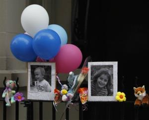 In this Oct. 27, 2012 file photo, photographs of the two children allegedly stabbed by their nanny are displayed at a memorial outside the apartment building were they lived in New York.