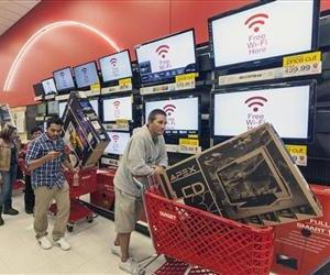 Shoppers walk past a TV display at a Target store in this file photo.
