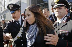 Karima el-Mahroug is escorted outside the Milan's Law court by two Carabinieri police officers after giving her testimony.
