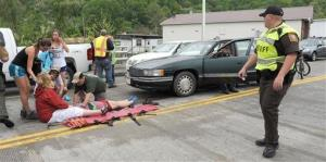 Emergency personnel respond to one of the people hit by a car, at right, during the beginning of the Hikers Parade at the Trail Days festival in Damascus, Virginia.