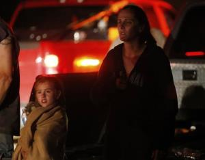 Seven-year-old Katrina Ash, left, watches with her mother  as heavy equipment is brought into their tornado-damaged neighborhood near Dale, Oklahoma.