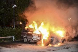 A car burns in the Stockholm suburb of Kista after youths rioted in several different suburbs around Stockholm for a third night.