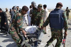 Security personnel carry a victim's belongings in Quetta, Pakistan on Thursday, May 23, 2013. A car bomb targeting a police vehicle killed 11 policemen and one civilian.