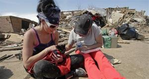Brittany Brown, left, and her grandmother Tracy Harville tend to Harville's cat, Kitty, after finding it in tornado rubble for two days at Harville's destroyed home, May 22, 2013, in Moore, Okla.