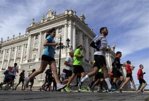 Runners pass by the Royal Palace as they take part in the 36th edition of the Madrid Marathon, Spain, Sunday, April 28, 2013.