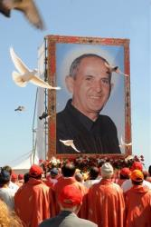Doves fly over the crowd in front of a giant picture of Rev. Giuseppe Puglisi during his beatification ceremony in Palermo, Sicily, Saturday.