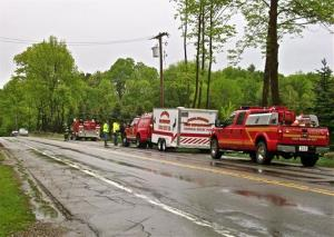 Emergency vehicles sit parked along the road in Ephratah, NY, Saturday, May 25, 2013, as the search for the pilot of a downed Angel Flight continues.