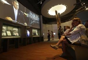 A woman wipes tears from her face as she and her sister watch a video in the exhibit dedicated 9/11 in the George W. Bush Presidential Library and Museum.