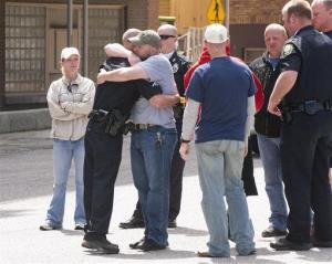 Area police officers console Bardstown Police officers in the parking lot of the Jefferson County Government Building.