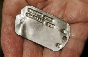 In this Wednesday, May 22, 2013 photo, World War II veteran Irving Mann displays his dog tag that was found and returned to him, in Rochester, NY.