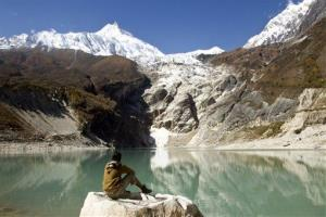In this file photo, a trekker sits by Birendra Lake in the Manaslu region, part of the Great Himalaya Trail route, in Nepal.