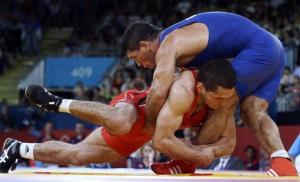 A 2012 photo shows Uzbekistan's Soslan Tigiev, in red, competing against Hungary's Gabor Hatos for the bronze medal in London.