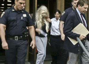 In an image made from video, actress Amanda Bynes, center, wearing sweats and a blonde wig, is escorted after a Manhattan criminal court appearance on Friday May 24, 2013 in New York.