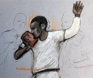 In this court artist sketch by Elizabeth Cook, suspect Michael Adebolajo kisses the Qu'ran, as he appears at Westminster Magistrates Court,  London, June 3, 2013.