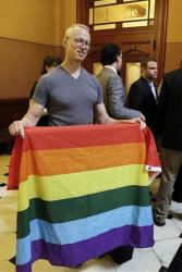 Andy Thayer of the Gay Liberation Network, displays a gay pride banner in a show of support of Illinois' gay marriage legislation outside the office of Illinois Speaker of the House Michael Madigan.