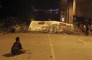 A protester sits on the ground as the Bosphorus Bridge is seen behind a barricade in Istanbul early this morning.