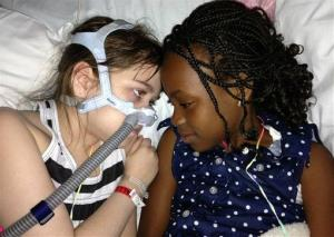 In this May 30 photo provided by the Murnaghan family, Sarah Murnaghan, left, lies in her hospital bed next to adopted sister Ella.