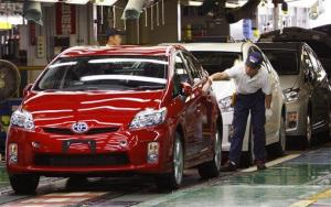 A Toyota worker checks a Prius coming off the assembly line in Japan.