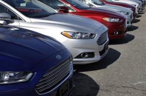 A row of Ford Fusion sedans sit in a lot at a Ford dealership in, Norwood, Mass.