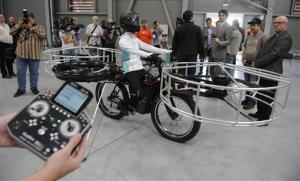 Journalists watch the flying bike, with a test dummy in the saddle in Prague.