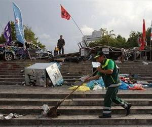 A municipality worker cleans the steps of Taksim Square under a barricade in Istanbul on Thursday, June 13, 2013.