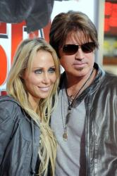 In this Jan. 9, 2010 file photo, Billy Ray Cyrus, at right, and his wife Laeticia Tish Finley, arrive to the premiere of The Spy Next Door in Los Angeles.