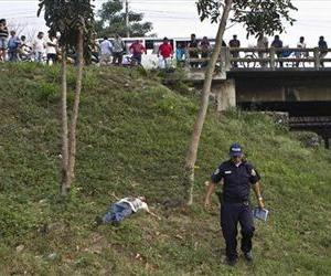 The body of Justiniano Lara, 51, lies dead on the adjacent area of a road in San Pedro Sula, Honduras, Monday, March, 25, 2013.