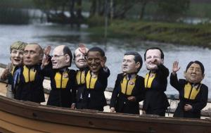 Anti-hunger activists, wearing giant head masks depicting the G-8 leaders, sail on a boat past the hotel where the G8 summit media center is located in Enniskillen, Northern Ireland.